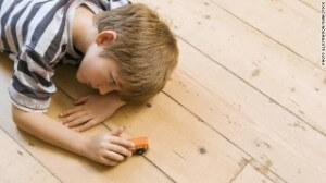 boy with autism laying on floor and playing with truck